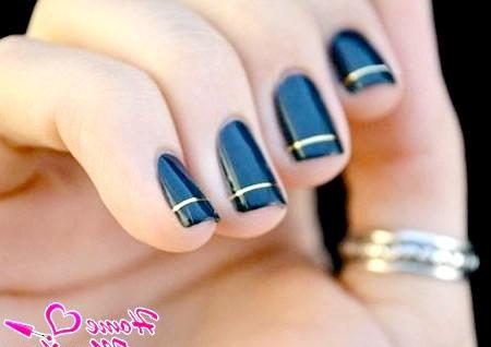 Фото - темно-сині нігті з золотими смужками