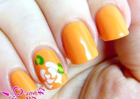 Фото - красива біла квітка на помаранчевих нігтях