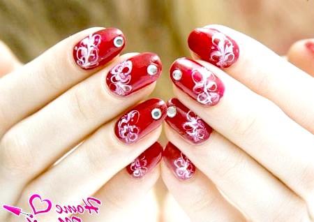 Фото - червоні нігті з білими візерунками