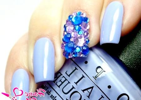 Фото - розсип декоративних кристалів на середньому пальці