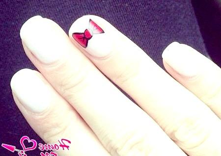 Фото - красивий червоний бант на білих нігтях