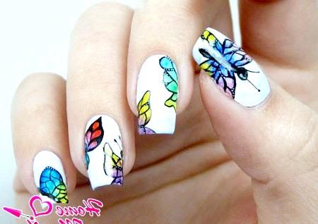 Фото - різнокольорові метелики на білих нігтях