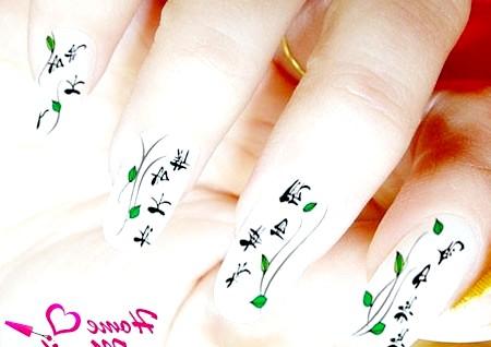 Фото - невеликі чорні ієрогліфи на білих нігтях